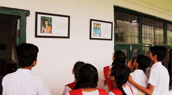 """Students look at teachers' life lessons displayed in a """"wisdom corridor"""" in their school."""