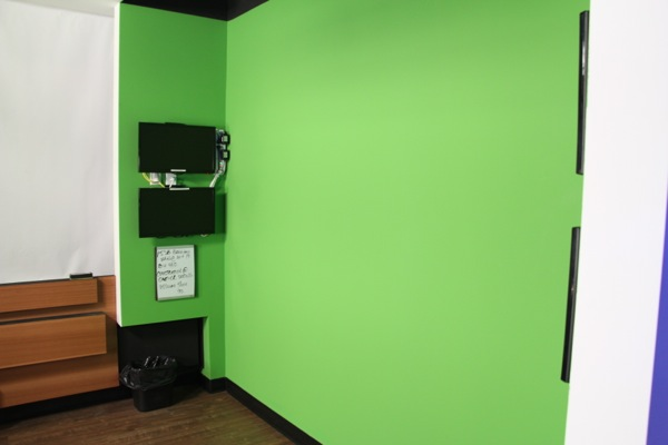 A small room between the studio and the editing suites has a wall painted green, and monitors on each side