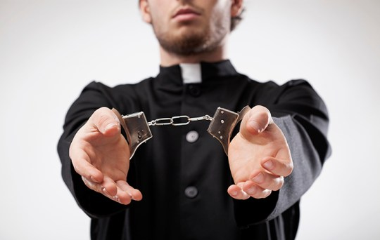 Young christian priest in cassock arrested and handcuffed