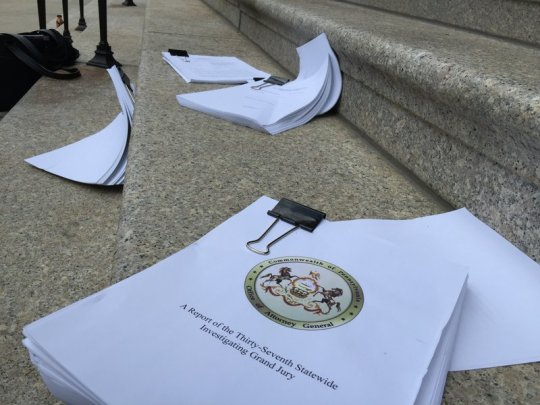 Clergy sexual-abuse grand-jury reports were strewn on the steps leading into the Cathedral Basilica of Saints Peter and Paul during Monday afternoon's press conference.