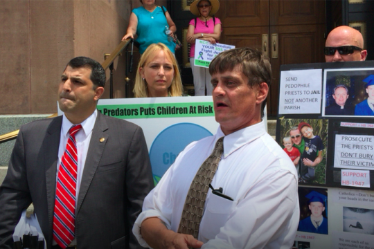 John-Michael Delaney, outspoken clergy sex-abuse victim, was supposed to meet with Archbishop Charles Chaput on Monday. Instead, state Rep. Mark Rozzi (left) flew him to Philadelphia to participate in a protest after that meeting was canceled. Behind Delaney stands sexual-abuse victim Kristen Pfautz Woolley.