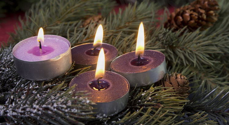 four lighted votive candles on a snowy pine branch