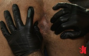 Submissive, gay slave is bent over and has an ass examination by a dominant man with gloves