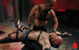 Gay man is bound in leather straps to an X cross and has his mouth covered by his Master