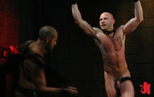 Chained man with melted wax over his chest gets flogged by his gay, dominating partner