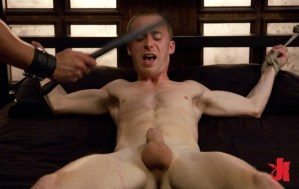 Tied up, muscular, gay man gets his balls lightly caned by his Master while lying on a bed