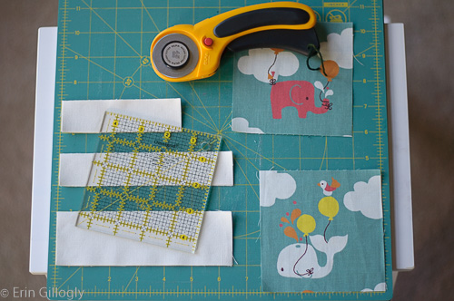 photo of a cutting board with cut fabric, a rotary cutter, and an acrylic ruler artfully arranged