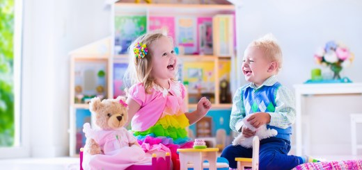 Kids playing with doll house and stuffed animal toys. Children sit on a pink rug in a play room at home or kindergarten. Toddler kid and baby with plush toy and dolls. Birthday party for little child.