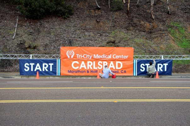 Workers clean the sign used at the Start of the Carlsbad Half Marathon