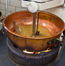 The century old gas fires, copper kettles and stirrers mix ingredients for brittle.