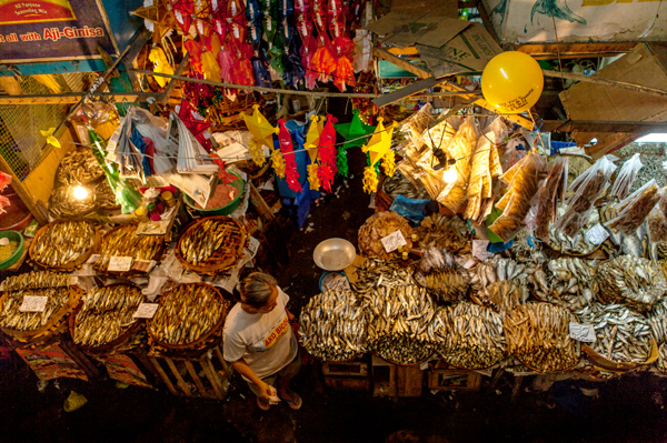Filipino woman shops for dried fish at night market.