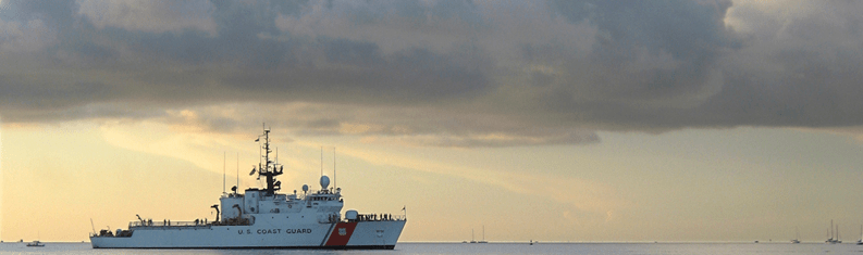 Coast Guard ship on horizon at dusk