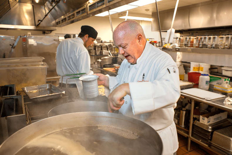 Chef Steven Miller cooking in large kitchen at Cornell University