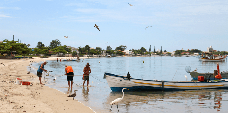 Brazilian beach with fishermen, small boat and birds in the sky