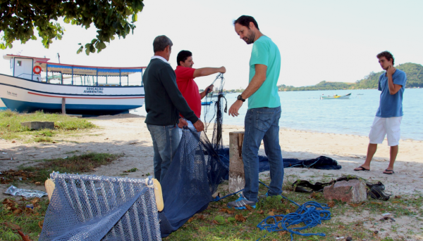 Four men on shore with fishing nets fitted with bycatch reduction devices