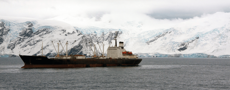 Krill fishing vessel on sea in front of icey mountains, Antarctica