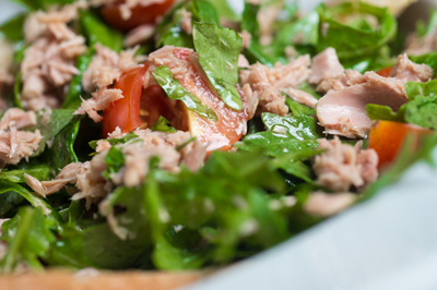 tuna salad in bowl with rocket and tomatoes