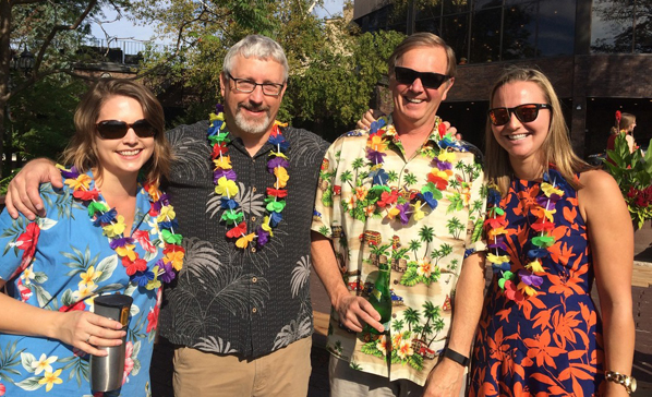 Four people pose for photo wearing Hawaiian leis