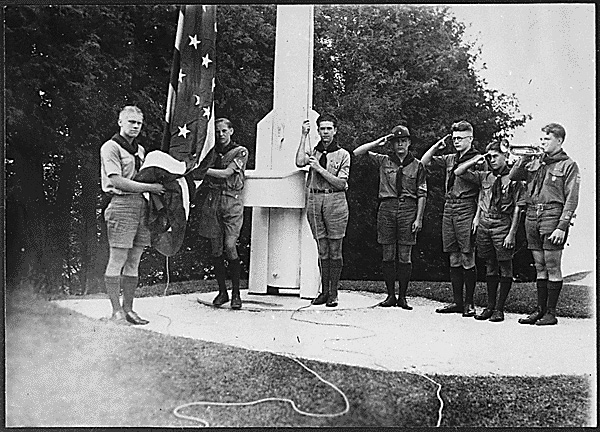 Gerald R. Ford (left) holds the flag as he and his fellow members of the Eagle Scout Guard of Honor prepare to raise the colors over Fort Mackinac at Mackinac Island State Park, Mich. The troop served as guides during the summer months of 1929.