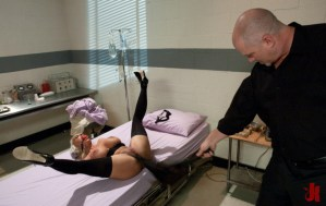 Sexy nurse with ball gag and stockings is flogged in the hospital room by patient