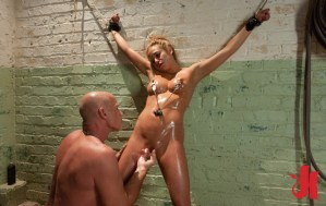 Submissive blonde with nipple clamps is chained to a wall and has her pussy fingered by a man
