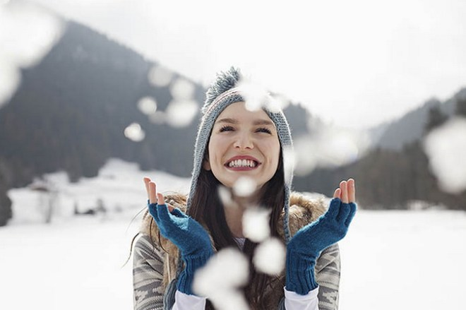 Happy woman enjoying falling snow in field