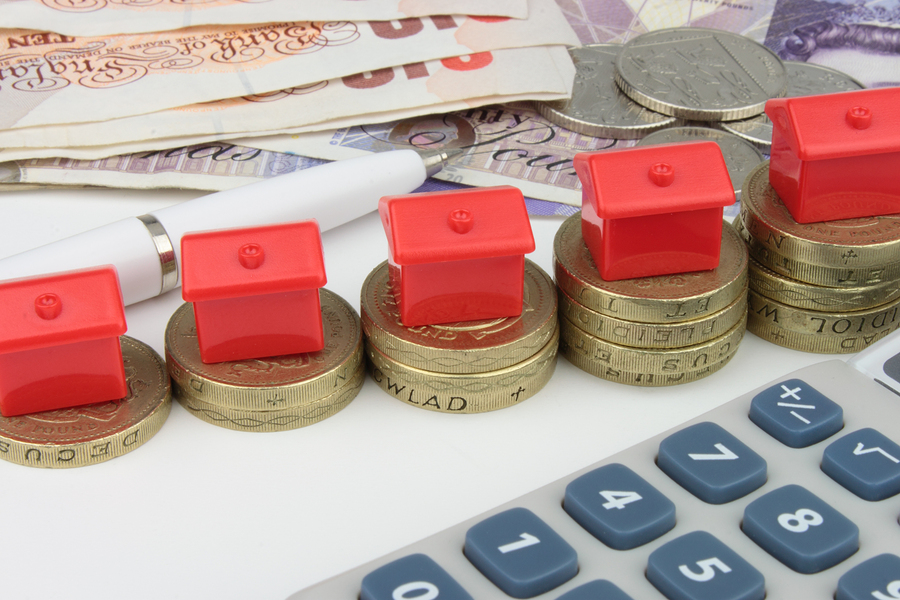 Red houses sitting on stacks of coins, with a pen and calculator to symbolize house finance in the U.k.