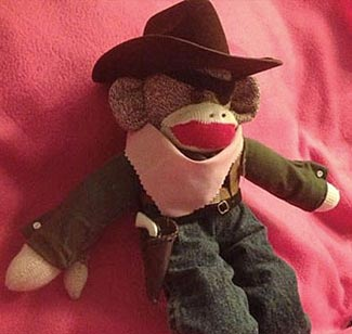 Making us Saferer :  The TSA seized the teensy tiny plastic gun from this sock monkey, claiming it to be a 'realistic replica'.