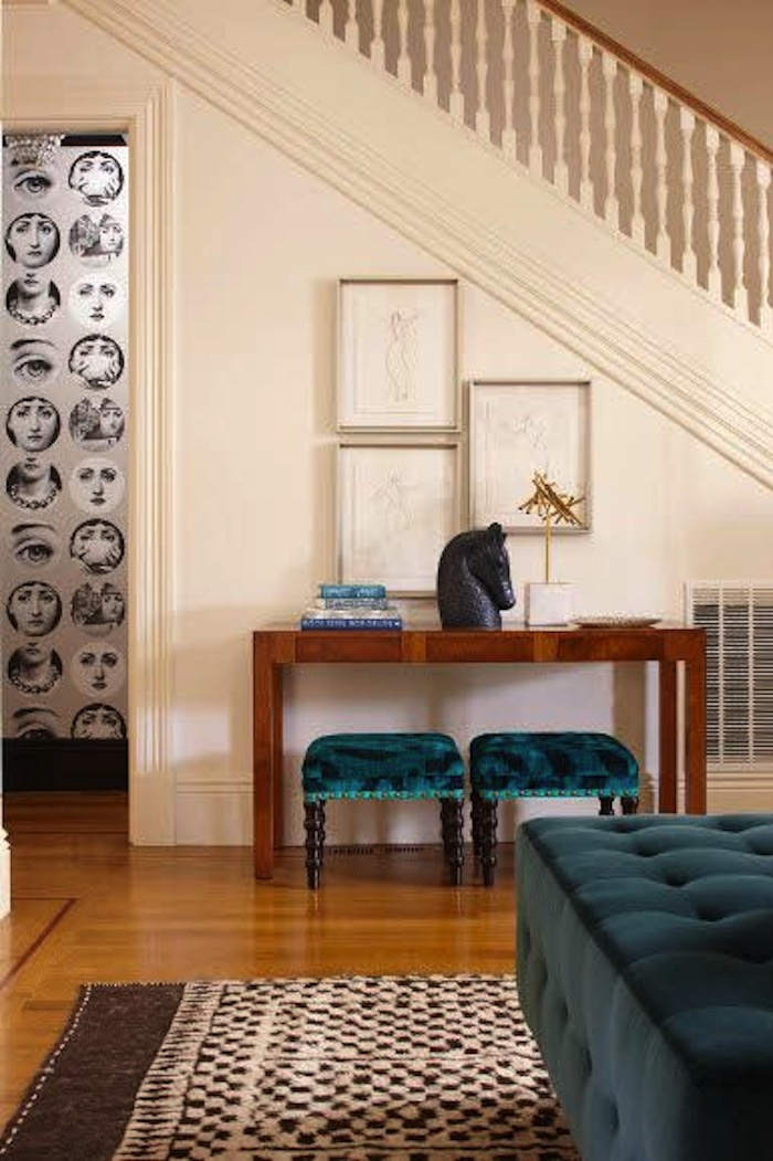 Modern wood console table fits perfectly below the staircase in this