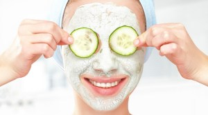 Funny young girl with mask for skin face and cucumbers