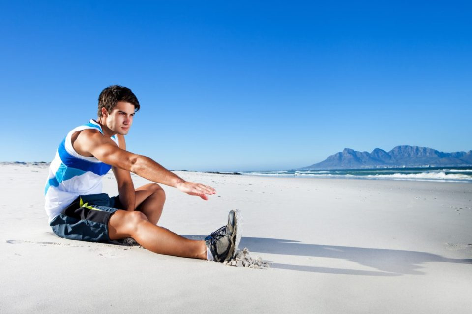 Fit young man stretching on sand at beach