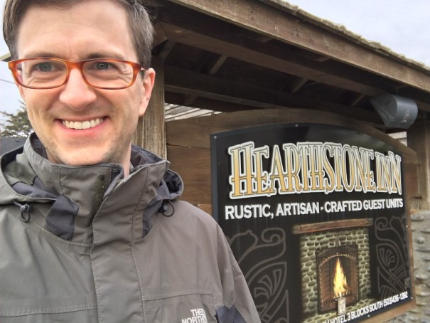 Nick stands in front of a sign that reads 'Rustic, Artisan-Crafted Guest Units'