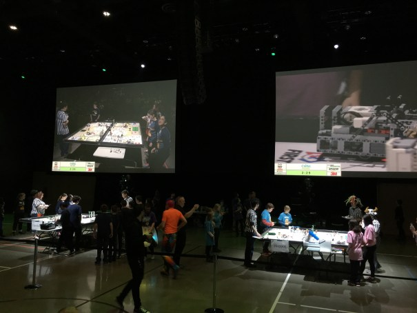 Two large projection screens show close up Lego robot action on the tables set up in the foreground.