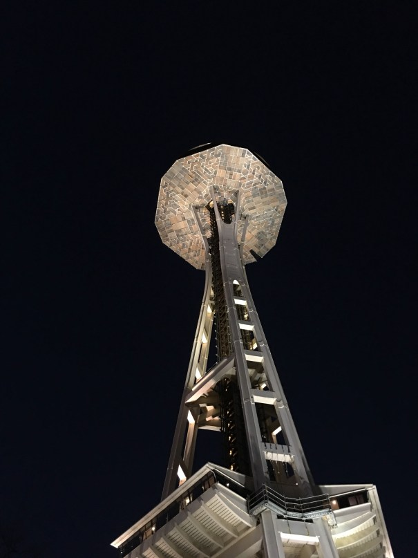 The Space Needle at night lit from below highlighting the triangular seams between plywood panels of the semi-regular dodecagon scaffolding under the crown.