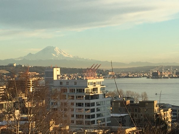 Mount Rainier in the haze over the red cranes of the Port of Seattle viewed from the north at the top of the Kinnear Park stairs off Olympic Place.
