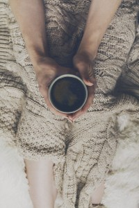 woman-hands-holding-tasty-warm-coffee-espresso-in-ceramic-cup-sitting-on-bed-with-plaid-home-concept-top-view_1220-1821