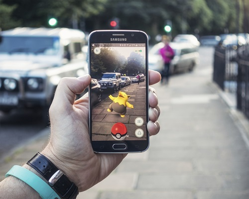 Edinburgh, UK - July 18, 2016: Closeup of a man holding a Samsung S6 smartphone, playing Pokemon Go with the game's augmented reality superimposing a character onto the pavement surface, as a person approaches in the distance.