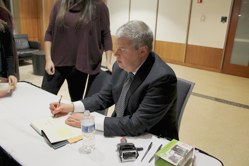 """Author Daniel Handler, known by his pseudonym Lemony Snicket, signs copies of """"A Series of Unfortunate Events"""" before speaking to students at the Elliott School on Thursday. Jordan McDonald   Hatchet Photographer"""