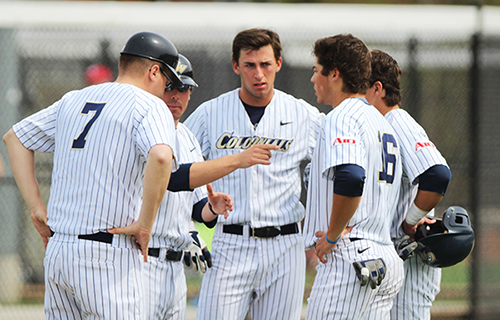 The Colonials discuss strategy in a game against UMass last season. The Colonials split a double-header against NJIT in this season's opening on Saturday. | Photo by Zach Montellaro | Hatchet staff photographer