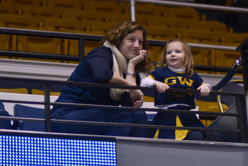 Lisa DeBow, an alumna from the Class of 1997, and her daughter Caroline DeBow Rohen, dressed as a GW cheerleader, cheer on the Colonials.