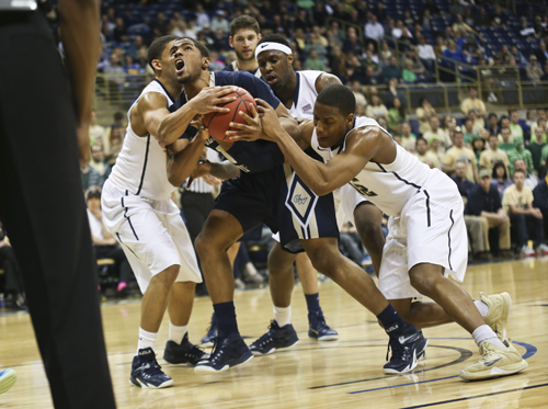 Junior Kethan Savage fights off defenders in GW's first-ever NIT win against Pitt in March. Savage has expressed a desire to transfer from the program after three years at GW. Cameron Lancaster | Photo Editor