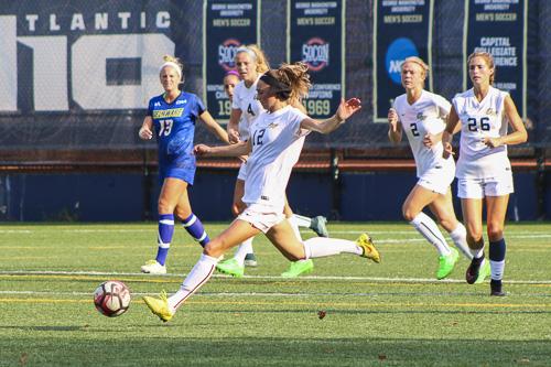 Senior Mackenzie Cowley kicks the ball in GW's win against Delaware. Jordan McDonald | Senior Staff Photographer