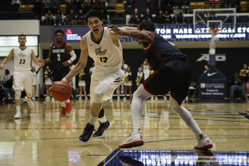 Junior guard Yuta Watanabe drives the ball to the hoop against Duquesne on Wednesday. He led GW with 15 points during the team's win. Ethan Stoler | Hatchet Photographer