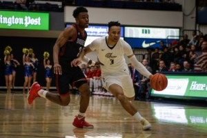 Freshman guard Jair Bolden dribbles around a Dukes defender. The game marked the first career start for Bolden who finished with five points, four assists and four rebounds. Ethan Stoler | Hatchet Photographer