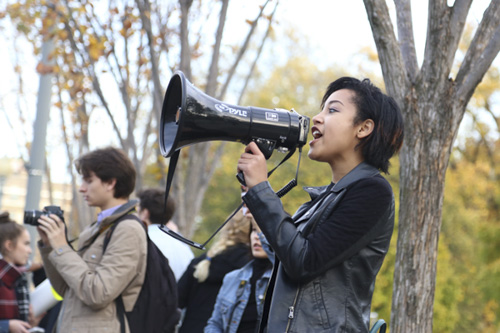 Keiko Tsuboi, ESIA-U, a leader of the protest, uses a microphone to align the supporters in front of the White House. Keegan Mullen | Hatchet Photographer