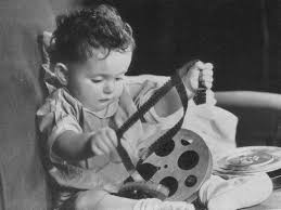 A baby pulls 16mm film loose from a film reel.