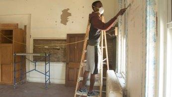 student scrapes paint in Fairbanks building