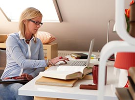 Woman on laptop with book open