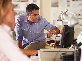 Man sitting on desk with computer