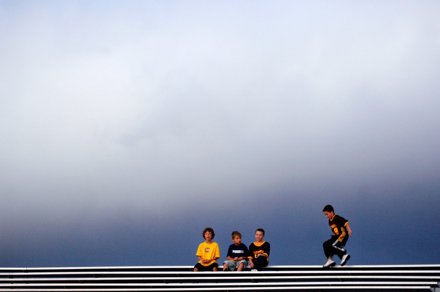 ADAM GERIK/JOURNAL STAR  East Peoria fans sit high atop the lonely bleachers at Peoria Stadium as the Raiders take on the Woodruff Warriors on Friday.